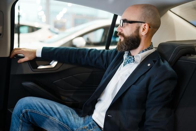 Człowiek sprawdza komfort tylnych siedzeń w nowym samochodzie, salonie samochodowym. klient w salonie samochodowym, mężczyzna kupujący transport, firma dealera samochodowego dealer