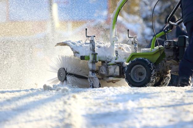Człowiek sprzątający ulicę od śniegu ręczny traktor specjalny