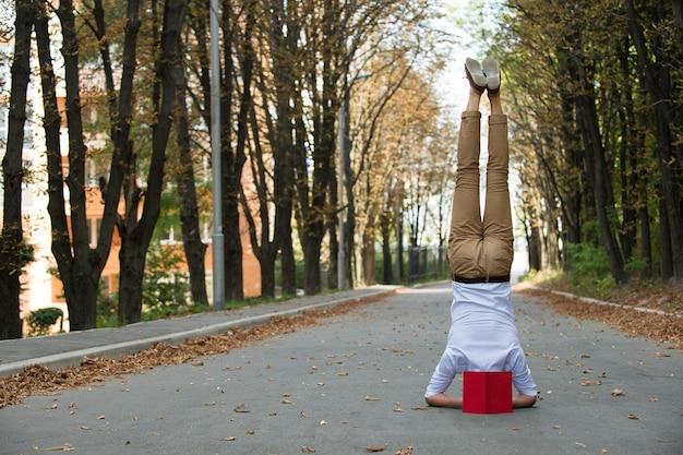 Człowiek stać na głowie na parkowej drodze. student z książką do góry nogami jesienią na świeżym powietrzu. równowaga między życiem zawodowym i prywatnym. edukacja i wiedza. ćwiczenia jogi na głowie i sport.