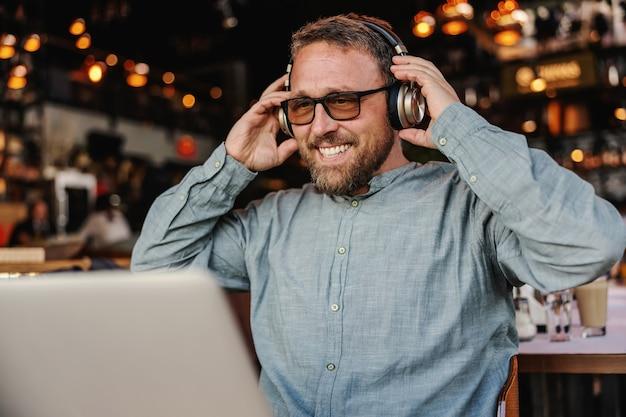 Człowiek, stawiając słuchawki siedząc w kawiarni.