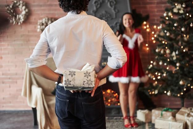 Człowiek stoi i trzyma pudełko za. kobieta w czerwonej sukience otrzyma teraz prezent świąteczny od chłopaka.