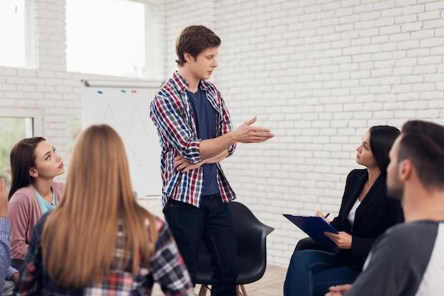 Człowiek stoi w kręgu kobiet i mężczyzn podczas sesji.