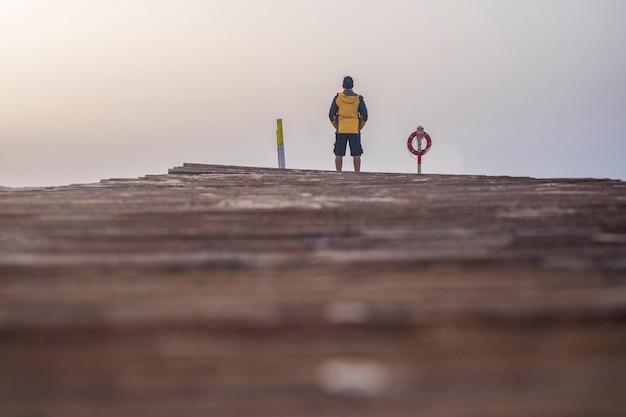 Człowiek stojący na końcu drewnianej podłogi i ścieżki patrząc na morze. ciesząc się alternatywnymi wakacjami wczesnym rankiem z pięknym niebem z przodu. wanderlust i alternatywna koncepcja wakacji