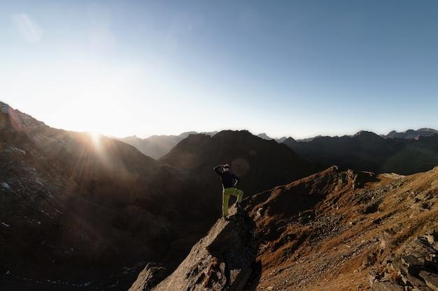 Człowiek stojący na skale na szczycie góry w obliczu słońca