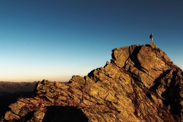 Człowiek stojący na szczycie skały w ciągu dnia