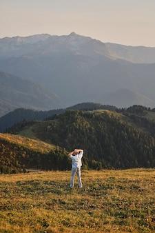 Człowiek stojący na szczycie skały z powrotem do kamery, jego ramiona na stronach ładne góry