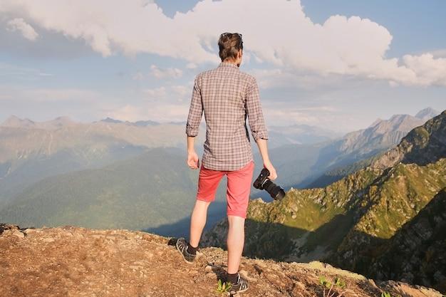 Człowiek stojący na szczycie skały z powrotem do kamery, ramiona na boki