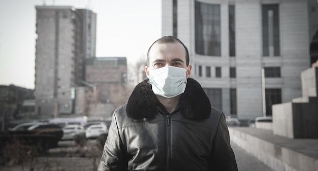 Człowiek stojący na zewnątrz w masce medycznej.