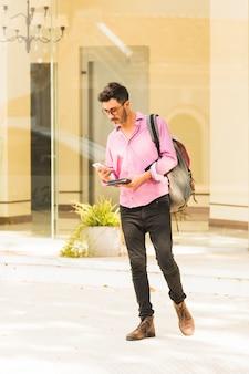 Człowiek stojący na zewnątrz z plecakiem za pomocą telefonu komórkowego