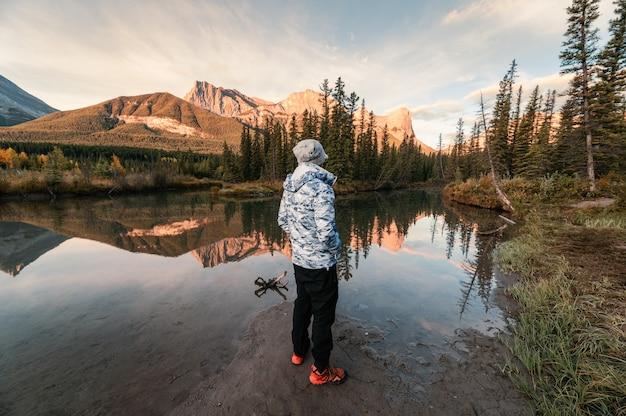 Człowiek stojący podróżnik podziwiający krajobraz góry trzech sióstr, odbicie na rzece jesienią w canmore, kanada