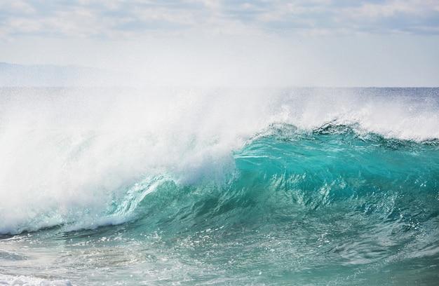 Człowiek stojący przed morzem na molo z dużą falą bijąc pluskiem w czasie sztormu