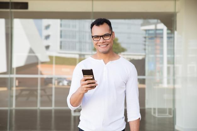 Człowiek stojący w budynku biurowym, trzymając w ręku telefon, uśmiechając się