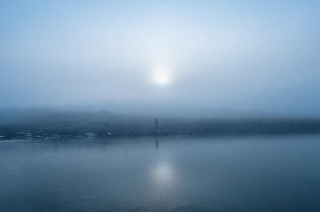 Człowiek stojący w mglisty nad jeziorem rano. tajemnice jak ze snu we mgle