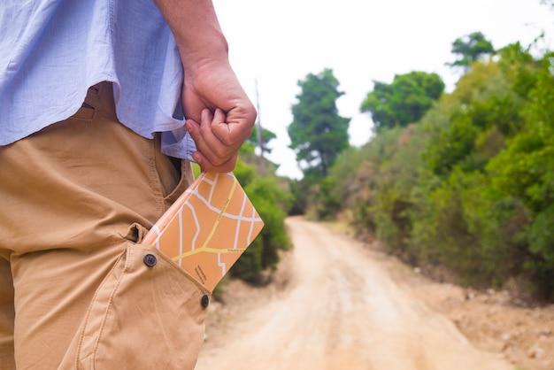 Człowiek stojący z mapą podróży w kieszeni z tyłu z miejsca na kopię.