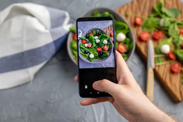 Człowiek strzelanie sałatką ze świeżych warzyw z mozzarellą i szpinakiem na aparat w telefonie komórkowym. gotowanie