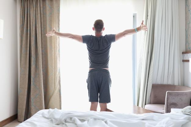 Człowiek sukcesu stoi w sypialni przy jasnym oknie