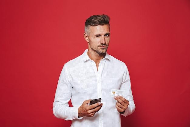Człowiek sukcesu w białej koszuli, trzymający kartę kredytową i smartfona na czerwonym tle