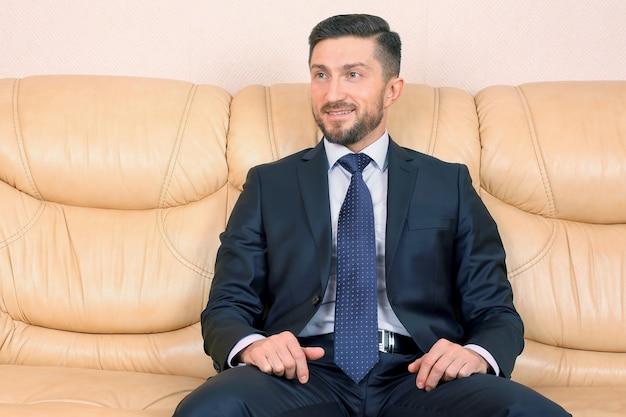 Człowiek sukcesu w biznesie siedzi na skórzanej kanapie