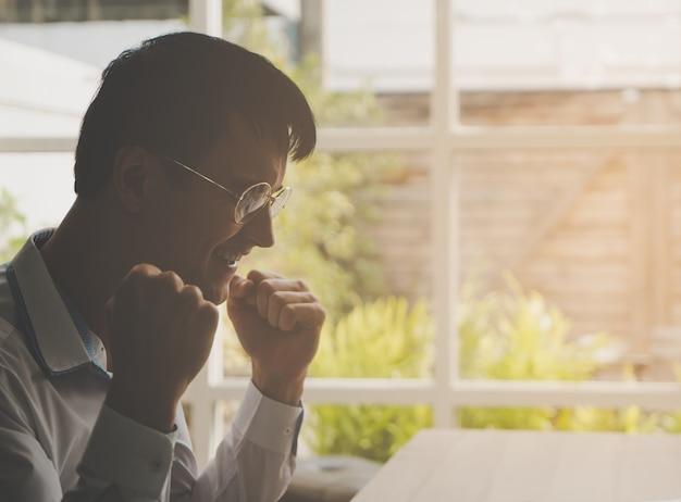 Człowiek sukcesu w biznesie z dwoma ręką wygrywając gest