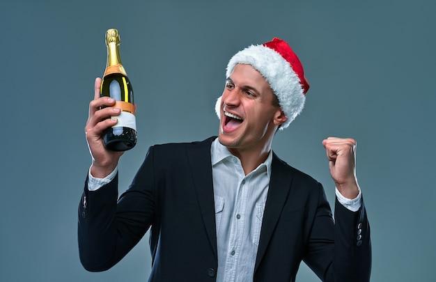 Człowiek sukcesu w marynarce i świątecznym kapeluszu z butelką szampana świętuje nowy rok i mówi tak. studio fotograficzne na szarym tle.