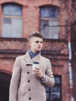 Człowiek sukcesu w płaszczu trzyma kawę na tle starego budynku