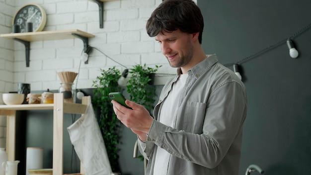 Człowiek surfuje w internecie przy użyciu telefonu stojącego w kuchni