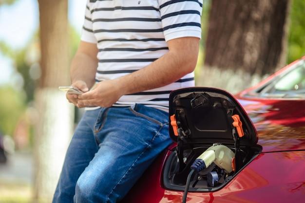 Człowiek świadomy ekologicznie ładujący swój pojazd elektryczny.