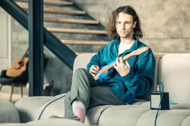 Człowiek tonujący struny. przystojny, niezwykły mężczyzna ubrany w stylowy strój, ćwiczący swoje umiejętności gry na gitarze podczas odpoczynku na kanapie