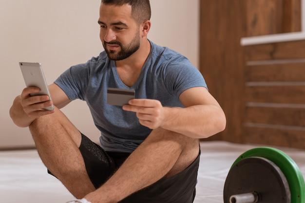 Człowiek trener fitness ze smartfonem i kartą debetową lub kredytową, kupując sprzęt online