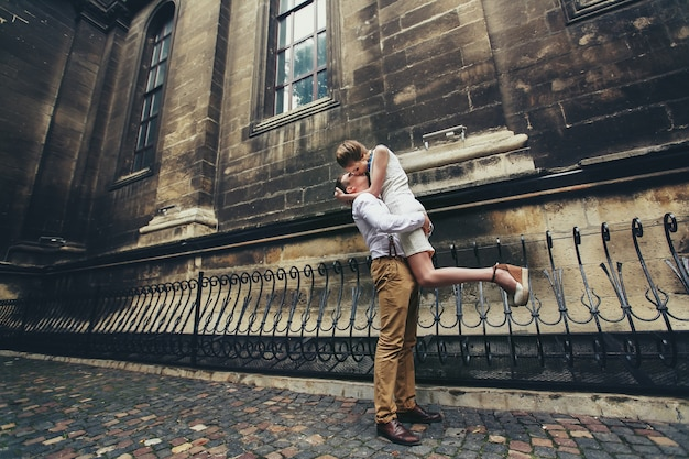 Człowiek trzyma damę shis, całując ją przed kościołem