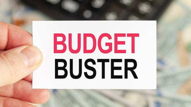 Człowiek trzyma kartkę papieru z tekstem buster budżet, koncepcja biznesowa