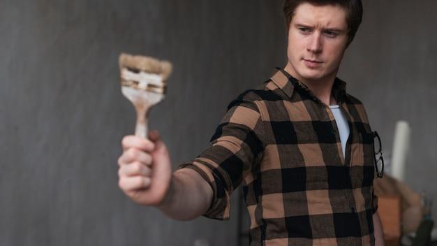 Człowiek trzyma pędzel malarski