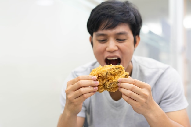 Człowiek trzyma rękę i pokazuje smażony posiłek z kurczaka do jedzenia