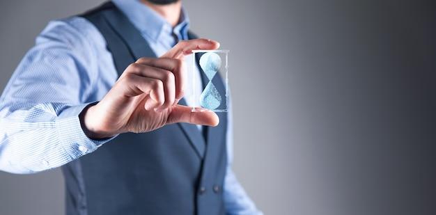 Człowiek trzyma w dłoni ikonę klepsydry. czas upływa.