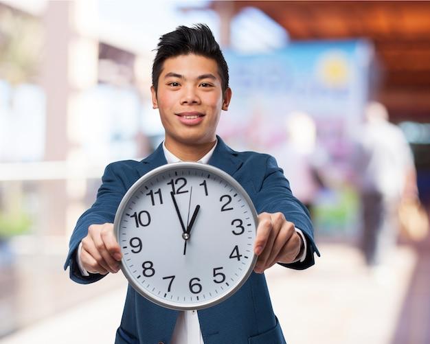 Człowiek trzyma wielki zegar