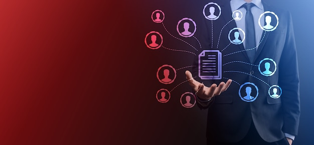 Człowiek trzymać ikonę dokumentu i użytkownika. firmowy system zarządzania danymi dms i koncepcja systemu zarządzania dokumentami. biznesmen klika lub publikuje na dokumencie powiązanym z użytkownikami korporacyjnymi.