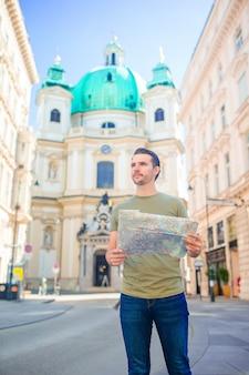 Człowiek turystyczny z mapą miasta i plecak w europie ulicy.