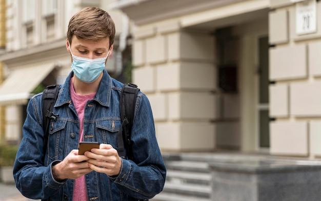 Człowiek ubrany w maskę na zewnątrz z miejsca na kopię