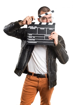 Człowiek ubrany w skórzaną kurtkę trzymającą klapperboard