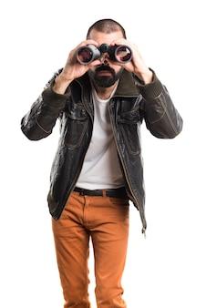 Człowiek ubrany w skórzaną kurtkę z lornetką