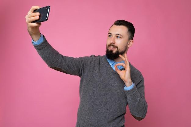 Człowiek ubrany w stylowe ubranie, stojący na białym tle nad ścianą, trzymając smartfon, biorąc zdjęcie selfie, patrząc na ekran telefonu komórkowego.
