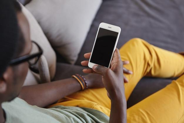 Człowiek ubrany w żółte dżinsy relaks w domu, leżąc na wygodnej kanapie