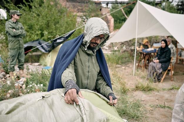 Człowiek-uchodźca nakrywający namiot workiem
