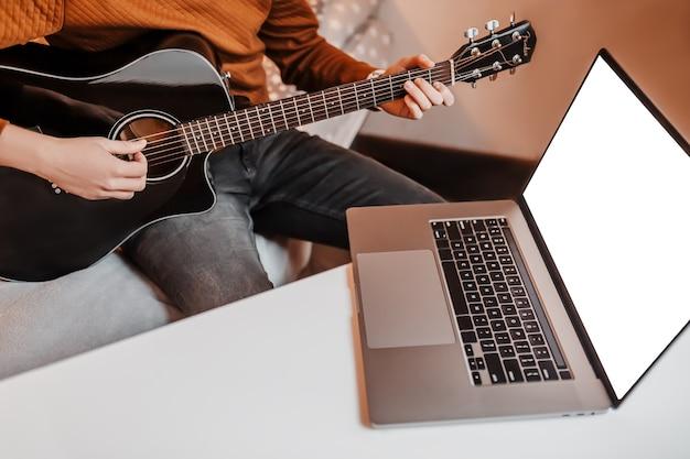 Człowiek uczący się gry na gitarze za pomocą nauki online w domu. facet siedzi przy stole z laptopem i czarną gitarą