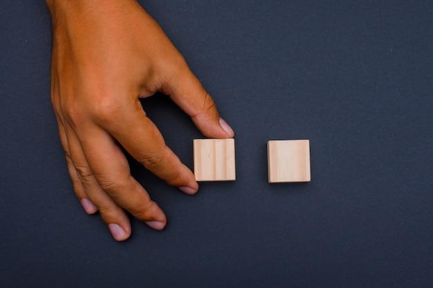 Człowiek umieszcza drewniane kostki.