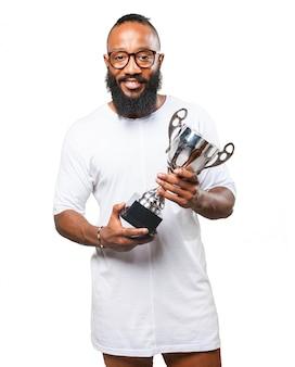 Człowiek uśmiechnięty ze srebrnym trofeum