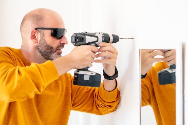 Człowiek ustanawiające dziurę w ścianie za pomocą wiertarki