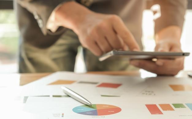 Człowiek używa tabletów do analizy zadań za pomocą pióra i wykresów na stole.