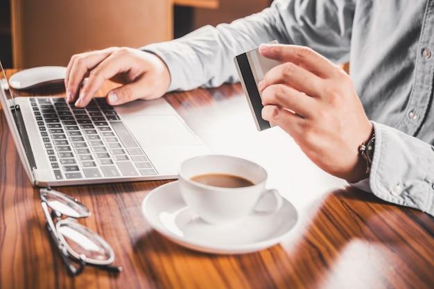 Człowiek używając swojego laptopa i posiadania karty kredytowej