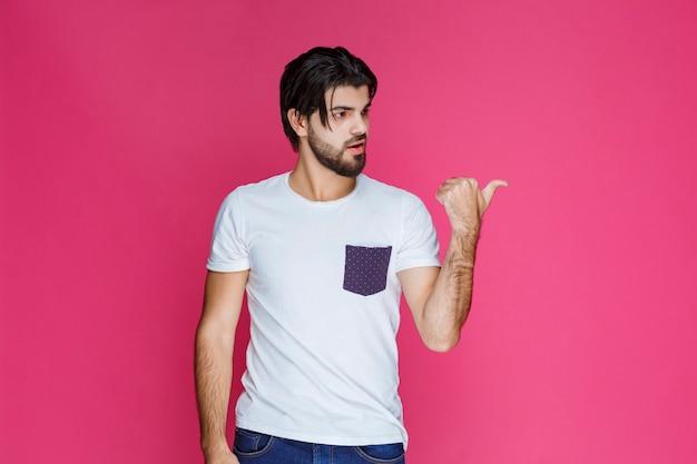 Człowiek w białej koszuli co kciuk w górę ręką znak.